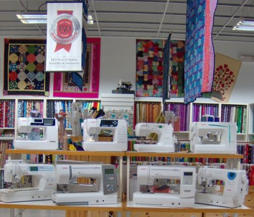 Beautiful quilts hanging and Janome sewing machines on display
